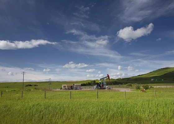 Beautiful landscape with green grass, blue sky and pumpjack. Photo is taken on sunny day of summer in Alberta, Canada.